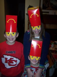 Kids wearing Happy Meal boxes as hats.